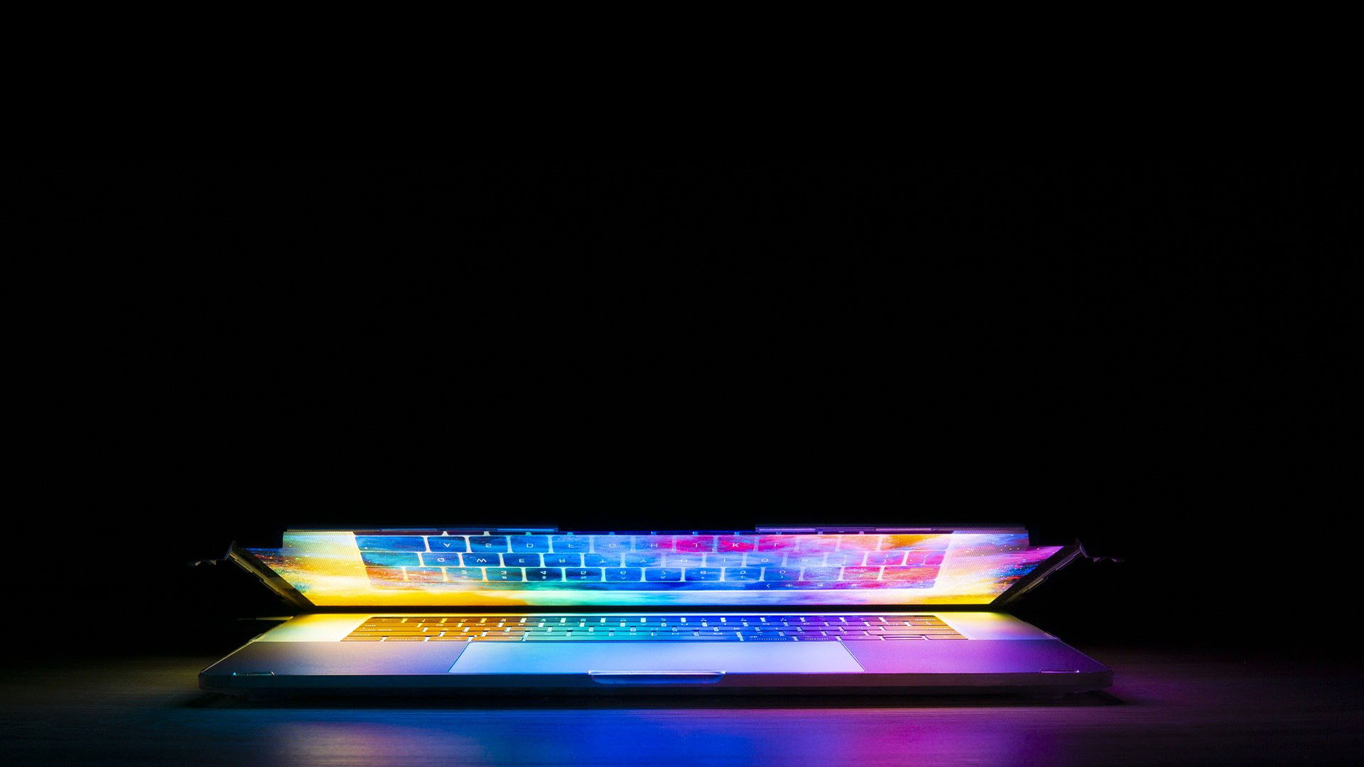A laptop glowing with a variety of colours.
